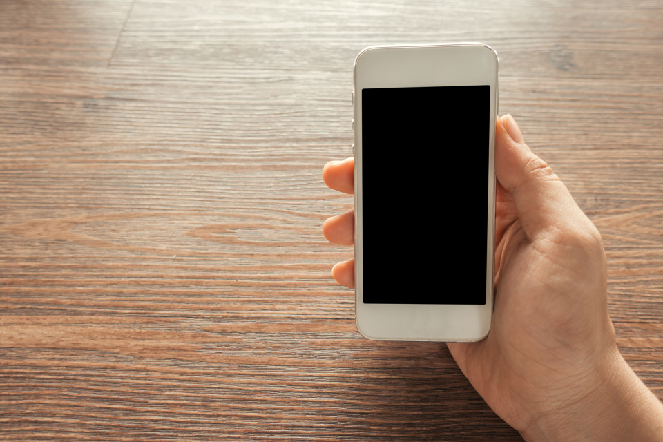 Cropped image of person showing mobile phone at desk